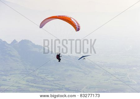 Paraglider and hand glider above mountain