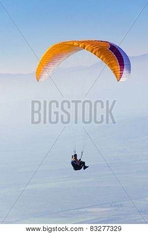 Orange paraglider flying against the blue sky