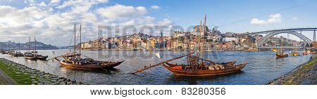 The iconic Rabelo Boats, the traditional Port Wine transports, with the Ribeira District and the Dom Luis I Bridge over the Douro River. Porto, Portugal. Unesco World Heritage.