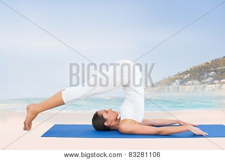 Fit woman doing the plough posture in fitness studio against beautiful beach and blue sky