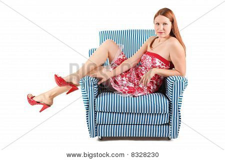 woman wearing dress and high-heel shoes sitting in striped armchair.