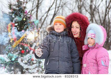 moeder en haar twee kinderen is permanent in de buurt van kerst boom