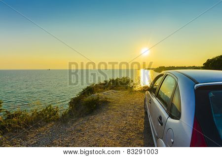 Sport car at sunset on a cliff with ocean view
