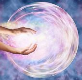 Female hands appearing to break through outer edge into ethereal circular energy formation depicting sending healing energy into embryo poster