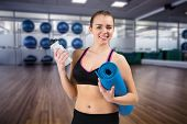 Fit brunette holding mat and sports bottle against large empty fitness studio with shelf of exercise balls poster