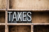 """The word """"TAXES"""" written in vintage metal letterpress type in a wooden drawer with dividers. poster"""