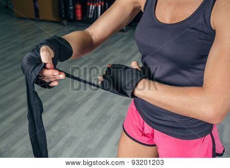 Woman wrapping hands with bandages before boxing training