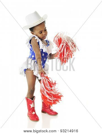 An adorable two year old shaking her pom poms while wearing a red, white and blue star studded outfit. On a white background.