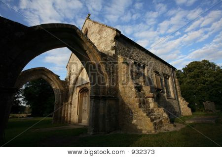 a ruined church in england below a beautiful sky in afternoon light. poster
