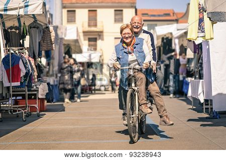 Happy Senior Couple Having Fun With Bicycle At Flea Market - Concept Of Active Playful Elderly