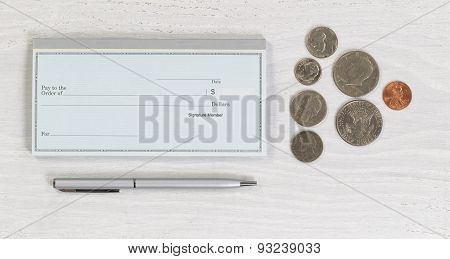 Blank Checkbook With Pen And Coins On White Desktop