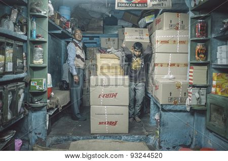 JODHPUR, INDIA - 07 FEBRUARY 2015: Shop owner and young worker in storeroom of tobacco shop with Miraj chewing tobacco in boxes. Post-processed with added grain and texture.