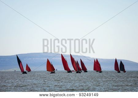 Traditional wooden boats Galway Hooker with red sail compete in regatta. Ireland.