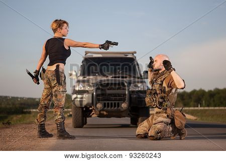 Rebellion woman with the gun is aiming on the soldier. Off-roader on the background. poster
