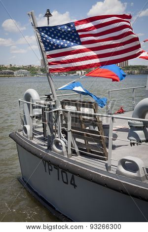 NEW YORK - MAY 22 2015: The American Flag waving from the stern of a US Naval Academy Yard Patrol Craft used for at-sea training and research purposes, moored at Pier 86 during Fleet Week NY 2015.