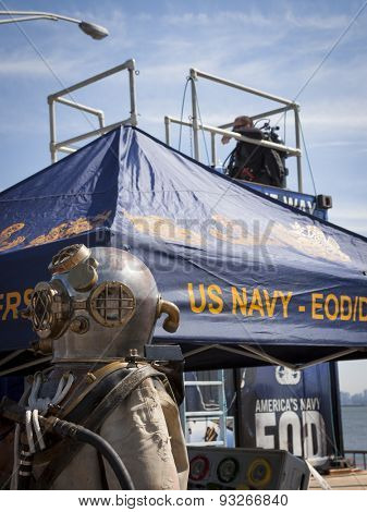 STATEN ISLAND, NY - MAY 24 2015: An early dive suit and helmet on display next to the US Navy EOD 6,800 gallon mobile dive tank on the Sullivans Pier in Staten Island during Fleet Week NY 2015.
