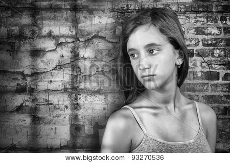 Sad and lonely teenage girl standing next to a grunge brick wall