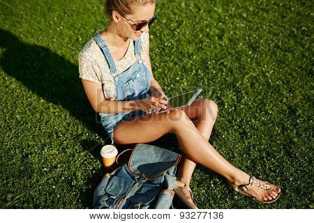 Young Blonde Girl Using Tablet Outdoor Sitting On Grass And Smiling. Student Using Digital Tablet Af