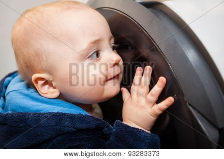 Portrait of a cute little baby boy looking with fascination inside the washing machine ** Note: Soft Focus at 100%, best at smaller sizes