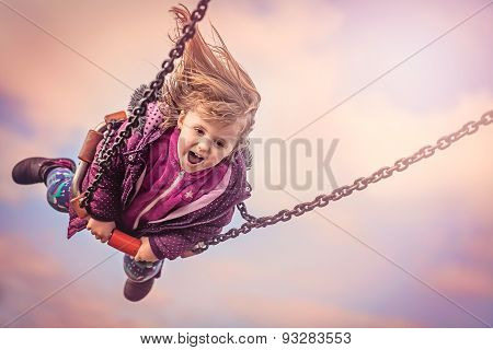 Young girl having fun on a sling in a playground ** Note: Visible grain at 100%, best at smaller sizes