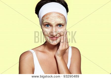 Young Woman With A Homemade Facial Mask On A Yellow