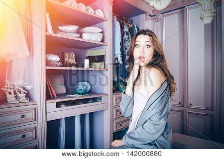 Beautiful young shocked woman don't know what to wear sitting in her closet