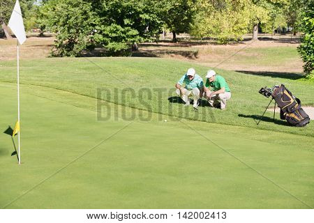 Two golfers chatting about putting shot, color image, horizontal