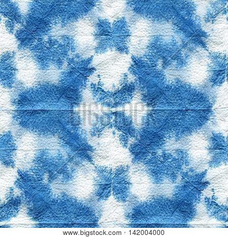 Seamless tie-dye pattern of indigo color with a geometrical ornament. Hand painting fabrics - nodular batik. Shibori dyeing.