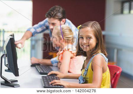Schoolgirl using computer in classroom at school