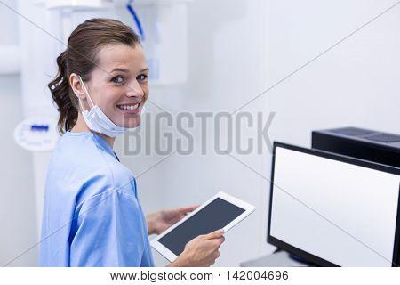 Portrait of smiling dental assistant holding digital tablet in dental clinic