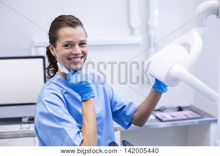 Portrait of smiling dental assistant adjusting light in dental clinic