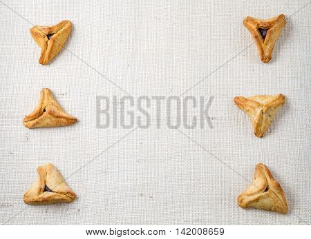 Jewish holiday of Purim. Hamantaschen cookies on canvas background with free space for text