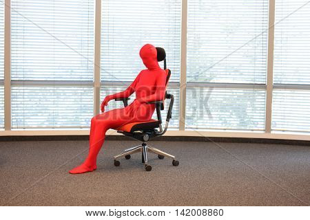 anonymous woman  in full body elastic suits sitting on armchair in office space