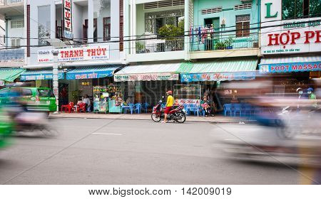 Can Tho, Vietnam - October 13, 2013: Can Tho street scene shops with shop houses above woman and children youth in red and yellow on motorscycle across street with blurred motion of passing vehicles on either side of frame. motorcycle across street with b