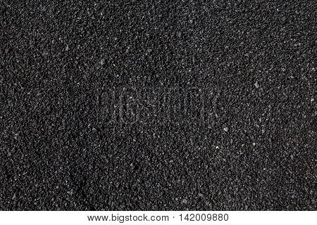 Black raw asphalt stones texture or background