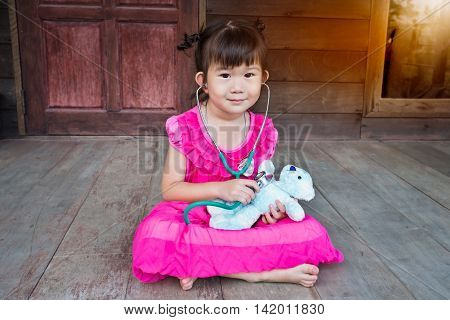 Adorable asian child playing doctor or nurse with plush toy bear at home. Happy girl listens a stethoscope to toy. Playful girl role playing.