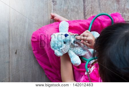 Top View Of Child Playing Doctor Or Nurse With Plush Toy Bear At Home.