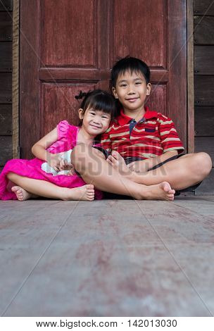 Asian kindly brother with his sister sitting and smiling happy together. Concept about loving and bonding of sibling. Happy family spending time together.