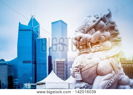 modern skyscrapers with a majestic stone lion in the foreground,hong kong,china.