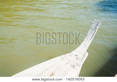 Head of wooden long tailed boat in river