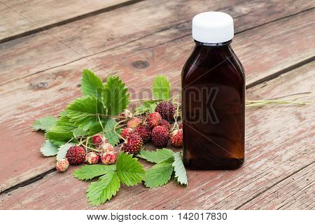 Medicinal plant Fragaria viridis with ripe berries and pharmaceutical bottle on old wooden table. In herbal medicine uses all parts of the plant (leaves flowers berries)
