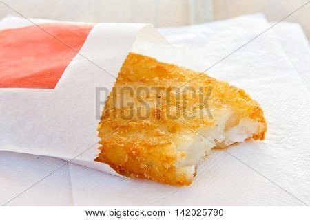 Single Partially Eaten Hash Brown In Paper Bag On White Napkin.