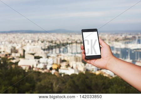 Men's hand holding smart phone against the backdrop of the view on Palma, Mallorca. Concept of excellent communication and fast Internet in distant places of the Earth. Place for text on the screen.