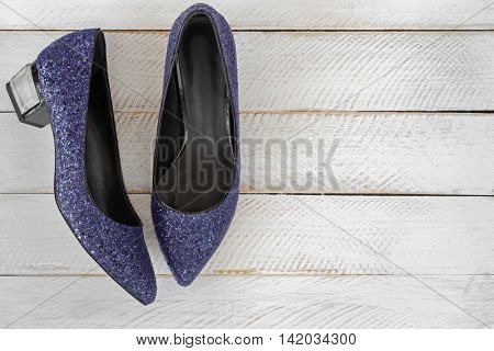 Top view of blue high-heeled shoes with glitters. A new pair of stylish sparkling beautiful shoes for ladies on white wooden background with copyspace