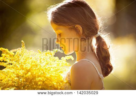 Little girl standing with a bouquet of yellow flowers