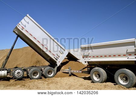 Two truck trailers  use hydraulic lifts to unload sand in a pile at a construction site