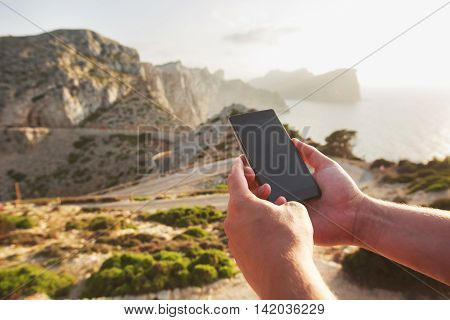 Men's hands holding and using smart phone in the mountains, Mallorca, Spain. Concept of excellent communication and fast Internet in distant places of the Earth.Place for text on the screen.