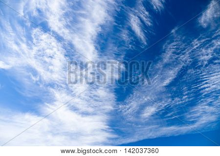 Bizzare cirrus and stratus clouds covering blue sky