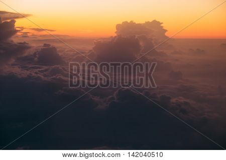 Photo of the Unreal sunrise over dark clouds through window airplane. Soft focus