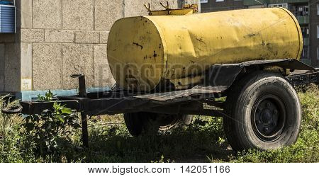 Cistern, water cistern, water tank, industrial water tank, water tank on wheels, old tank on wheels, tank on wheels for transporting liquids, yellow trailer